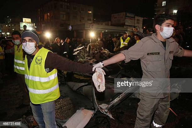 Lebanese emergency personel hold hands to delimit a security perimter around the wreckage of a minibus at the site of an explosion on February 3 2014...