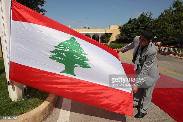 A Lebanese employee prepares to raise the national flag at the entrance to the Presidential Palace in Baabda southeast of Beirut while waiting for...