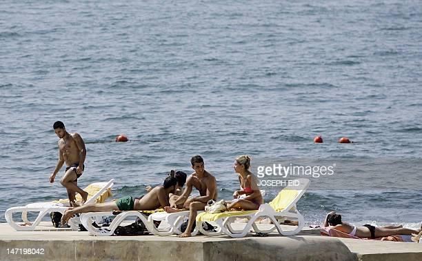 Lebanese enjoy sunbathing at a beach along the Mediterranean sea in Ain alMreisseh neighborhood of the capital Beirut on June 27 2012 AFP...