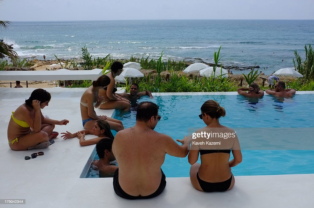 Lebanese enjoy the sun by the swimming pool at Lazy B beach resort in a secluded surrounding 20 minutes outside the capital on July 21, 2013 in Beirut, Lebanon. Despite the rising tensions between different Muslim factions in the country people enjoy their leisure time and continue their daily life as normal.