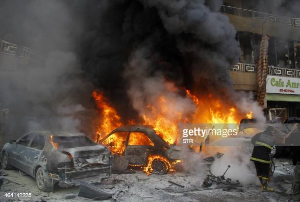 Lebanese firefighters extinguish fire from burning cars following an explosion on January 21 2014 in Haret Hreik a south Beirut neighbourhood...