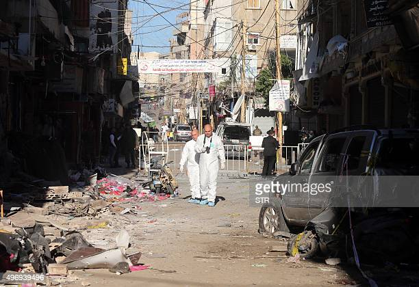 Lebanese forensic police investigate the site of a twin bombing attack that rocked a busy shopping street in the area of Burj alBarajneh a Beirut...