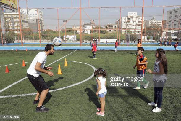 Lebanese Former alNejmeh football team captain Moussa Hjeij plays football with his children Heya and Naya and Mohammed at a football playground in...