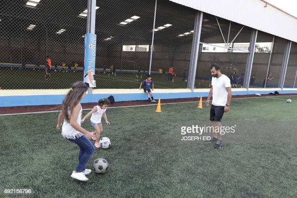 Lebanese Former alNejmeh football team captain Moussa Hjeij plays football with his daughters Heya and Naya at a football playground in Beirut on May...