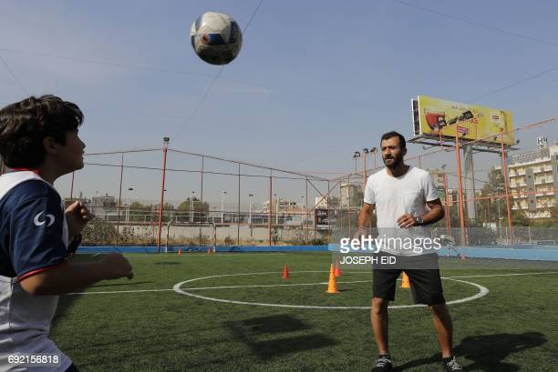 Lebanese Former alNejmeh football team captain Moussa Hjeij plays football with his son Ali at a football playground in Beirut on May 12 2017 / AFP...