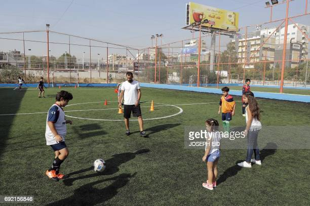 Lebanese Former alNejmeh football team captain Moussa Hjeij plays football with his children Heya and Naya and Mohammed and Ali at a football...