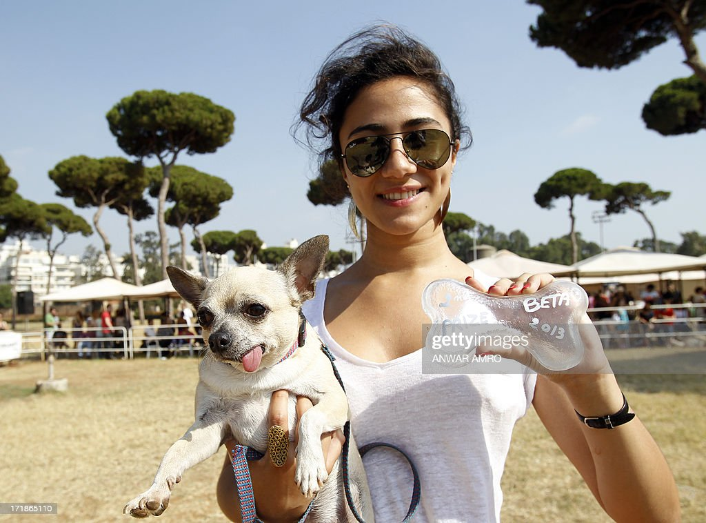A Lebanese girl holds her dog and a prize during the Beirut for the Ethical Treatment of Animals (BETA) dog show in Beirut, which holds contests to name 'best dog', 'cutest puppy', and 'best dog costume' in addition to 12 other categories on June 29, 2013. The show is one of BETA's major fundraisers to try to improve the welfare of animals in the region and to stop the abuse against them.