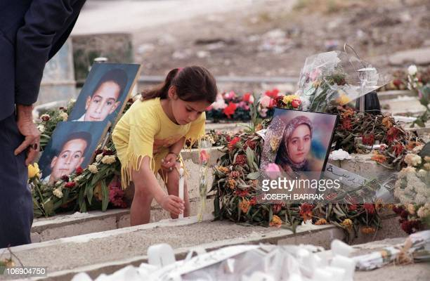 A Lebanese girl lights a candle on her teacher's tomb at Qana cemetary 10 May 1996 The teacher was one of the 105 civilians killed killed by Israeli...