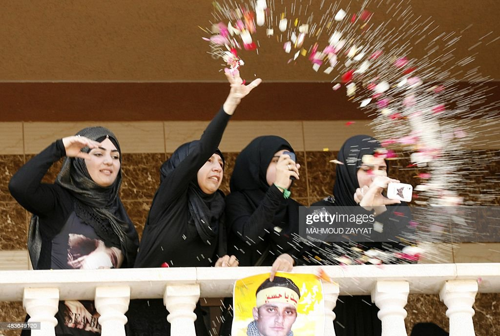 A Lebanese girl throws petals during the funeral procession of member of Lebanon's Shiite movement Hezbollah, Ali Manana, who was killed in combat alongside Syrian government forces fighting against Islamic State group jihadists in Syria's Zabadani area, on August 11, 2015 in Lebanon's southern village of Sarafand.