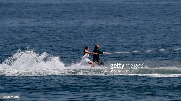 Lebanese groom and bride Tommy and Nadine water ski dressed in their wedding clothes in the waters off the bay of Jounieh north of Beirut on May 29...