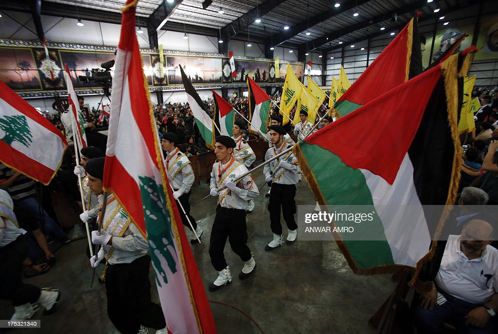 Lebanese Hezbollah members carrying the Lebanese and Palestinian flags parade during a gathering to mark the 'Al-Quds (Jerusalem) International Day' from Beirut's southern suburb neighbourhood of Rweiss on August 2, 2013. Hezbollah's chief Hassan Nasrallah made a rare public appearance at a Beirut rally held to mark Quds (Jerusalem) Day in support of the Palestinian people, an AFP photographer said.