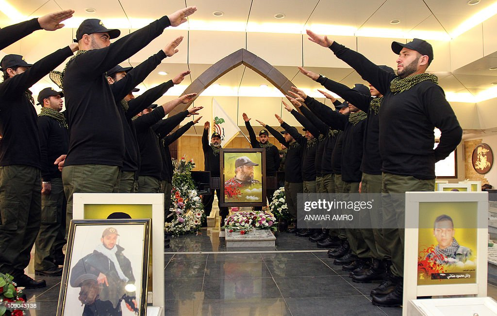 Lebanese Hezbollah militants gesture as they visit the grave of Hezbollah commander Imad Mughnieh who was killed in a car bombing in the Syrian...