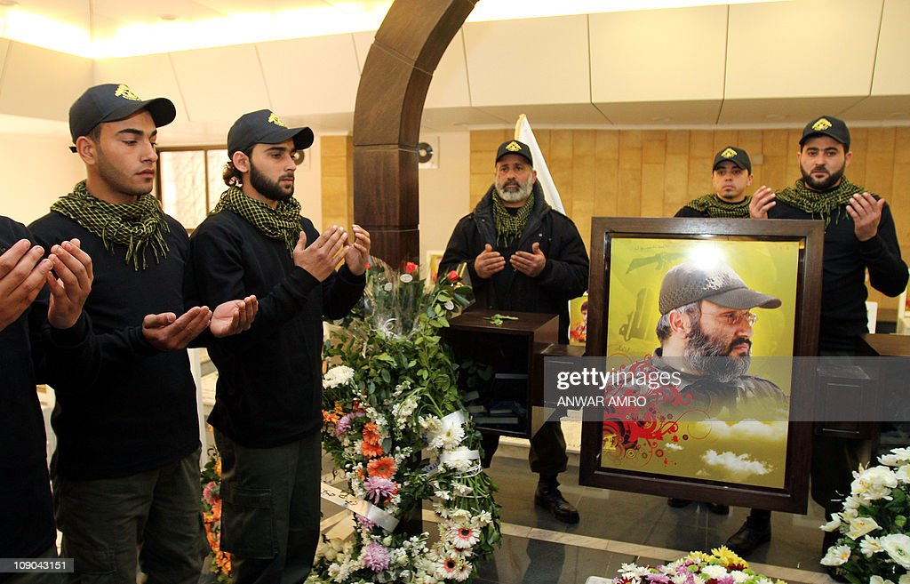Lebanese Hezbollah militants pray at the grave of Hezbollah commander Imad Mughnieh who was killed in a car bombing in the Syrian capital Damascus in...