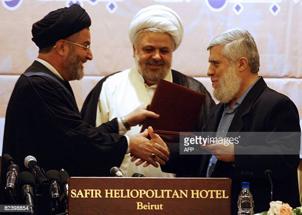Lebanese Hezbollah Shiite delagate Ibrahim Amin alSayed and Hassan alShahhal a representative of Lebanon's Sunni Salafists exchange the text of an...