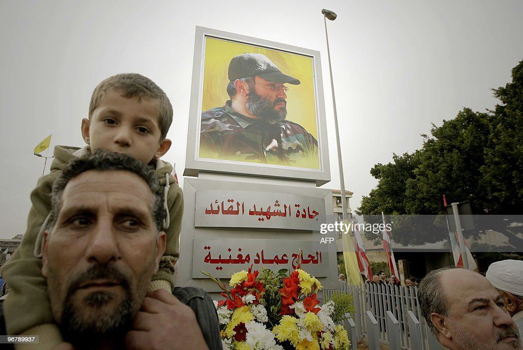 A Lebanese Hezbollah supporter carries his son on his shoulders next to a stand bearing a picture of Hezbollah's assassinated top commander Imad...