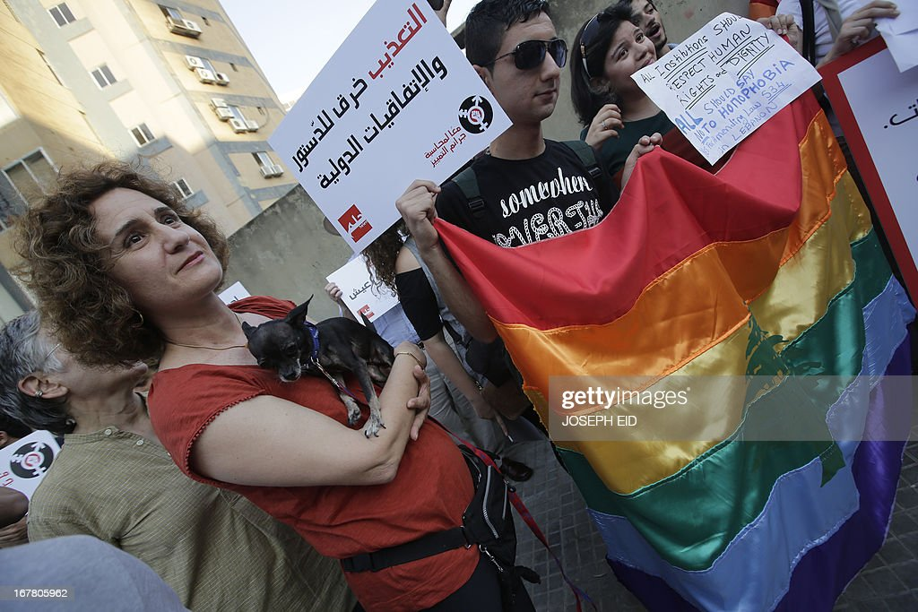 Lebanese homosexuals, human rights activists and members from the NGO Helem (the Arabic acronym of 'Lebanese Protection for Lesbians, Gays, Bisexuals and Transgenders') attend an anti-homophobia rally in Beirut on April 30, 2013 to condemn the arrest on the weekend of three gay men and one transgender civilian in the town of Dekwaneh east of Beirut at a nightclub who were allegedly verbally and sexually harassed at the municipality headquarters.