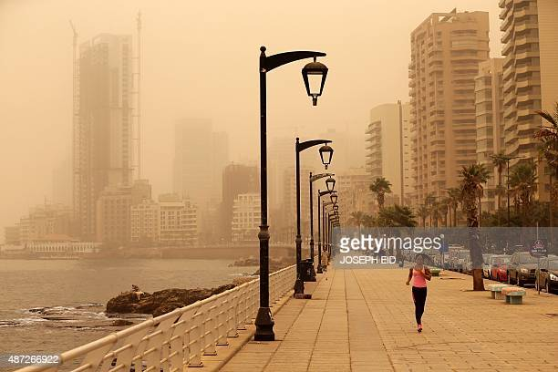 A Lebanese jogger runs despite the dust on the Corniche seaside promenade in downtown Beirut as a sandstorm blows over the Lebanese capital on...