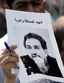 A Lebanese journalist holds a black and white picture of assassinated opposition writer Samir Kassir during a demonstration at Martyrs' square in...