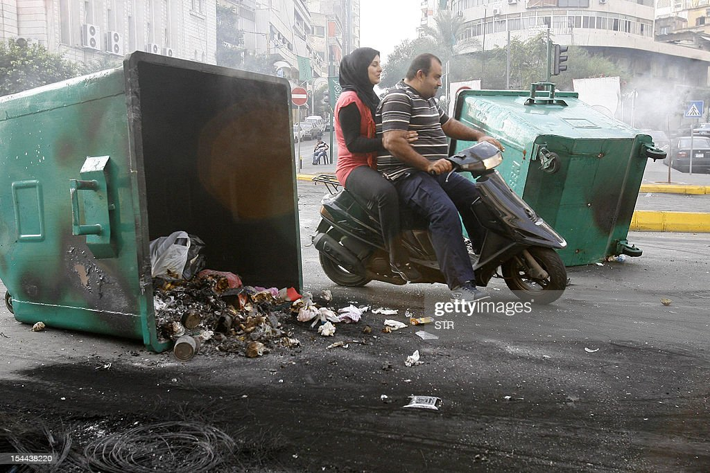 A Lebanese man and a woman ride a motorcycle past trash containers blocking a road in the Corniche al-Mazraa neighbourhood of Beirut on October 20, 2012 following a protest against a bomb blast the day before. Protesters cut off roads in several areas of Lebanon following the assassination of a high profile security official, AFP journalists said. AFP PHOTO/STR