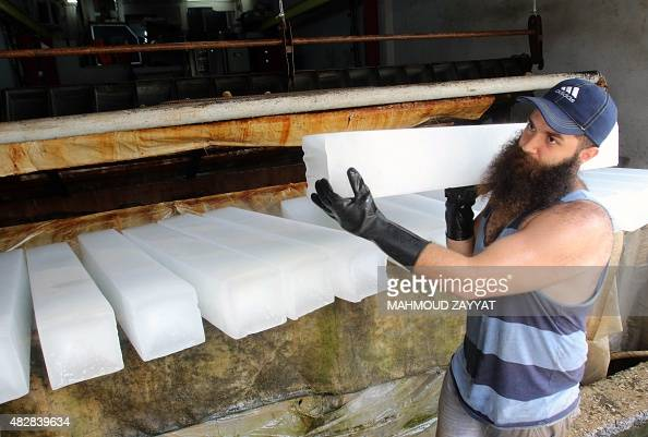 A Lebanese man carries a block of ice at his factory as the demand for ice increased in the southern Lebanese city of Sidon due to power cuts and the...