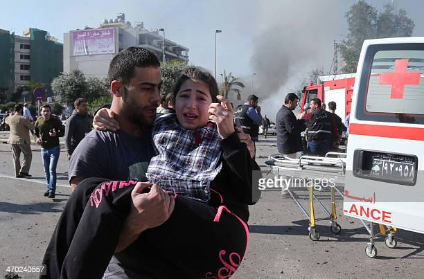 A Lebanese man carries an injured girl following a bomb explosion in a southern suburb of the capital Beirut on February 19 2014 Twin bomb blasts...