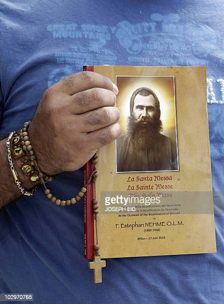 A Lebanese man carries the mass booklet for the beatification ceremony of Lebanese Maronite monk Estephan Nehmeh outside the Maronite Order's...