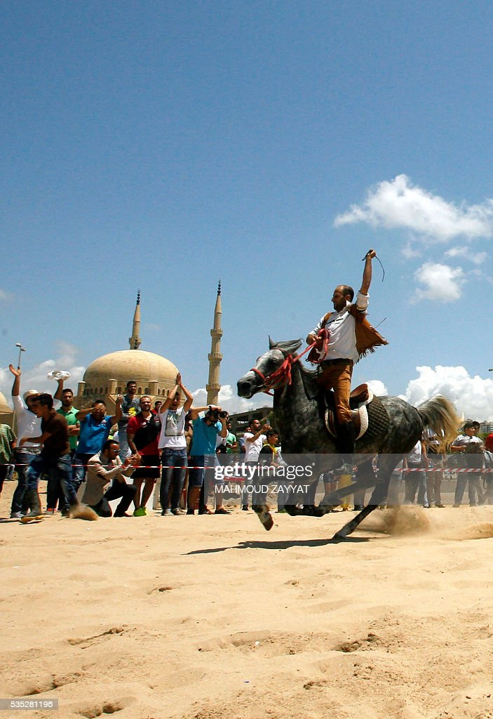A Lebanese man competes during a horse race festival on the coast shore of the city of Sidon, south Lebanon, on May 29, 2016. ZAYYAT