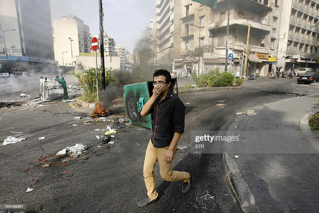 A Lebanese man covers his nose as he walks past burning tyres and trash containers blocking a road in the Barbir neighbourhood of Beirut on October 20, 2012 following a protest against a bomb blast the day before. Protesters cut off roads in several areas of Lebanon following the assassination of a high profile security official, AFP journalists said.
