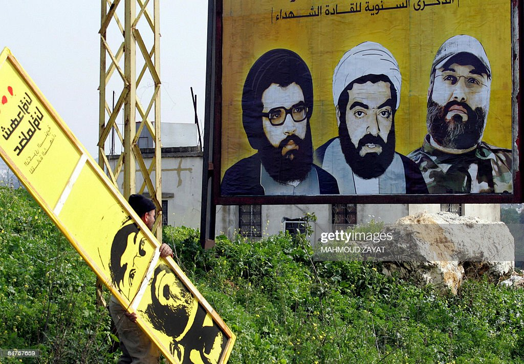 A Lebanese man hangs posters of slain Lebanese Hezbollah commanders Abbas alMussawi Ragheb Harb and Imad Mughnieh on the main road to the southern...