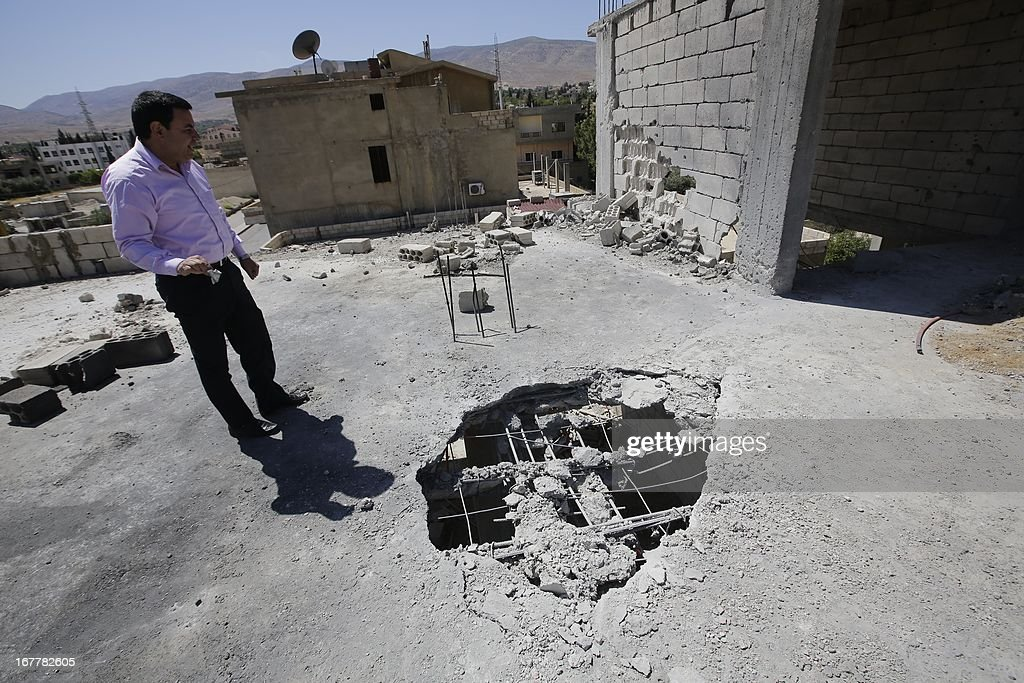 Lebanese man inspects the damage after a rocket coming from Syria fell on his house in the town of Hermel, a few kilometres from Baalbek in the Bekaa valley, on April 26, 2013. In their town of Baalbek, and other strongholds of Shiite movement Hezbollah in eastern Lebanon, its no longer a secret that the group's members are crossing the border to bolster the ranks of government troops battling rebels.