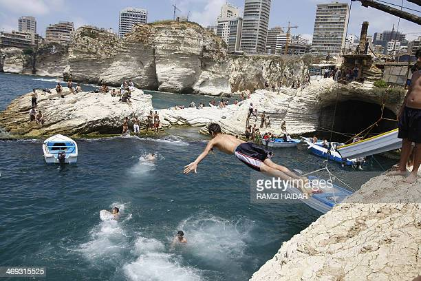 A Lebanese man jumps off a rock into the sea in Beirut on June 21 2009 AFP PHOTO/RAMZI HAIDAR