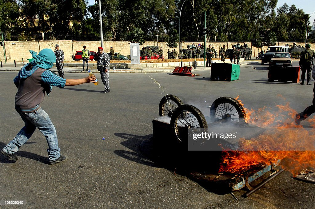 A Lebanese man pour fuel onto a burning cart in a neighborhood in the capital Beirut during a demonstration in support of the caretaker prime minister Saad Hariri on January 25, 2011, as hundreds of people converged on the northern city of Tripoli to take part in a 'day of rage' over the likely appointment as prime minister of Hezbollah-backed tycoon Najib Mikati.