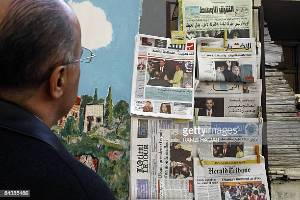 A Lebanese man reads the headlines of newspapers at a newsstand in Beirut on January 21 2009 The world hailed the dawning of the Barack Obama era at...