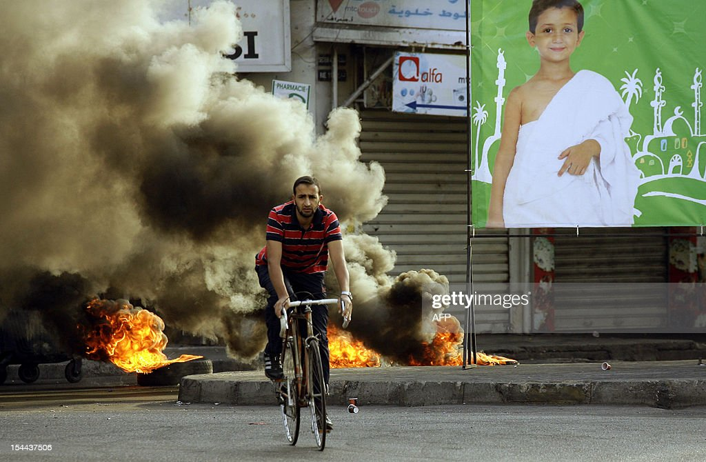 A Lebanese man rides a bicycle past burning tyres as demonstrators block a road in the southern city of Sidon on October 20, 2012 to protest against a bomb blast in the capital Beirut the day before. Protesters cut off roads in several areas of Lebanon following the assassination of a high profile security official, AFP journalists said.