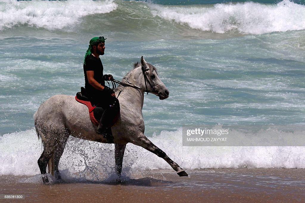 A Lebanese man rides a horse on the coast shore of the city of Sidon, south Lebanon, on May 29, 2016. ZAYYAT