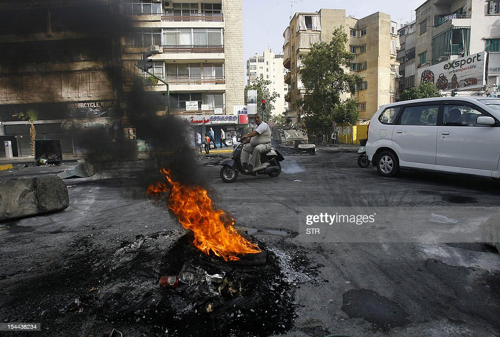 A Lebanese man rides a motorcycle past a burning tyre which was set on fire by protesters who blocked a road in the Corniche al-Mazraa neighbourhood of Beirut to protest against a bomb blast the day before on October 20, 2012. Protesters cut off roads in several areas of Lebanon following the assassination of a high profile security official, AFP journalists said.