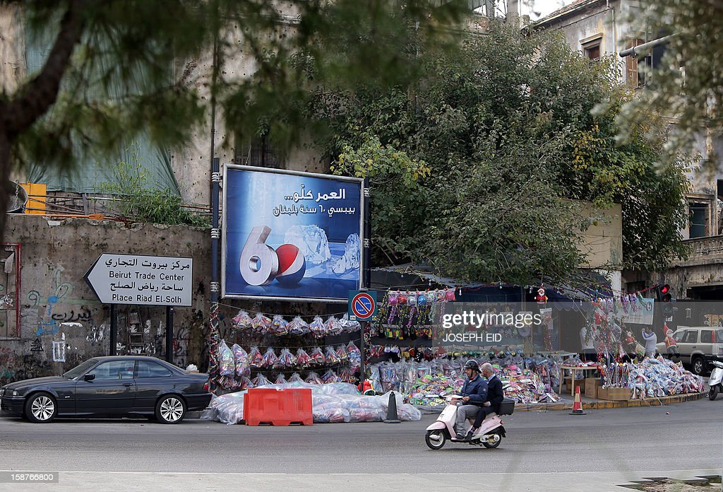 A Lebanese man rides his bike past a street shop displaying decoration for Christmas and New Year at a street in Beirut on December 28, 2012.