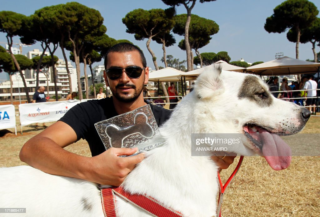 A Lebanese man shows off his award and dog at the arena during the Beirut for the Ethical Treatment of Animals (BETA) dog show in Beirut, which holds contests to name 'best dog', 'cutest puppy', and 'best dog costume' in addition to 12 other categories on June 29, 2013. The show is one of BETA's major fundraisers to try to improve the welfare of animals in the region and to stop the abuse against them.