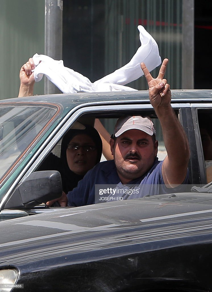A Lebanese man who managed to flee the area of clashes in Abra, near the southern Lebanese city of Sidon, flashes the sign for victory as his passenger waves a white cloth upon their arrival on the outskirts of the district on June 24, 2013. At least sixteen soldiers have been killed in clashes with supporters of Sheikh Ahmad al-Assir in southern Lebanon, the army said, in violence tied to rising sectarian tensions fanned by the Syria conflict.