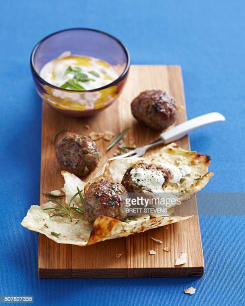 Lebanese meatballs on chopping board with dipping sauce