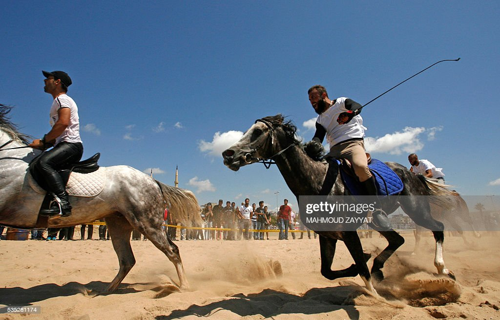 Lebanese men compete during a horse race festival on the coast shore of the city of Sidon, south Lebanon, on May 29, 2016. ZAYYAT