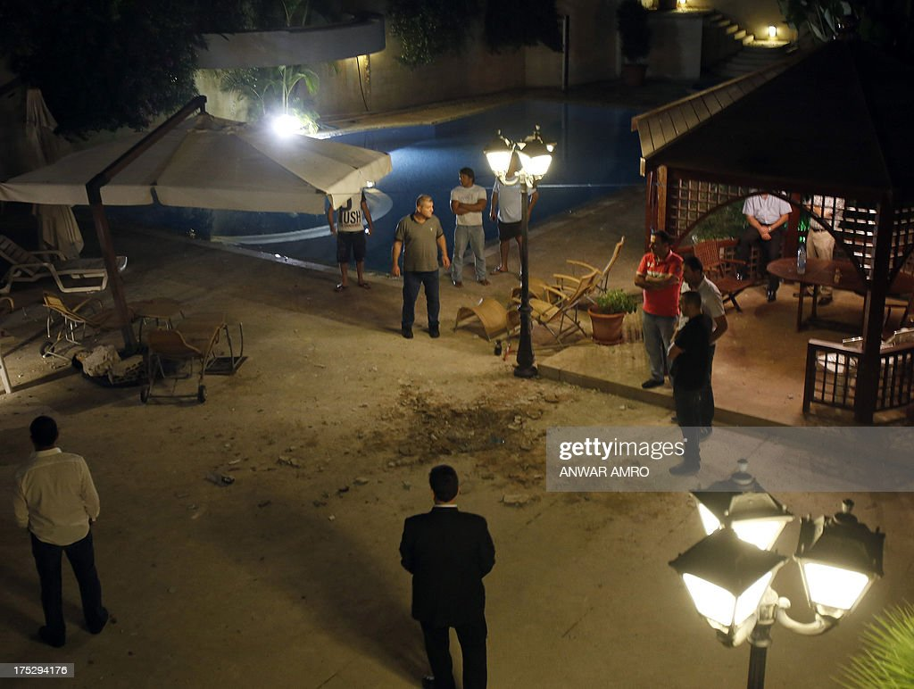Lebanese men inspect the damage at a private residence where one of two rockets fired from an unknown location exploded in the early hours of August 2, 2013, just metres from an entrance to the presidential palace in Baabda, around eight kilometres southeast of the Lebanese capital Beirut. The official news agency ANI said the second rocket fell near a Lebanese army training camp in the region of Baabda, causing no casualties as tensions mounted in the east Mediterranean country over the conflict in neighbouring Syria. AFP PHOTO / ANWAR AMRO