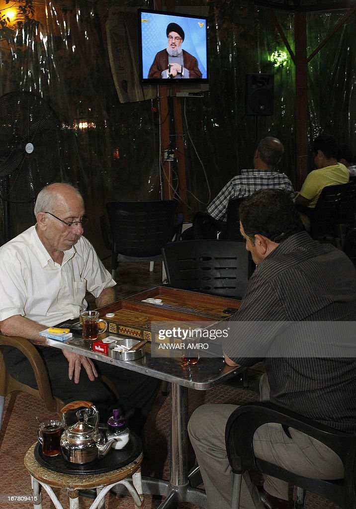Lebanese men play backgammon while others watch Hezbollah leader Hassan Nasrallah delivering a televised speech at a cafe in Beirut on April 30, 2013. The chief of powerful Lebanese Shiite Muslim party Hezbollah, a close Damascus ally, said that Syria's friends would not let the embattled regime of President Bashar al-Assad fall.