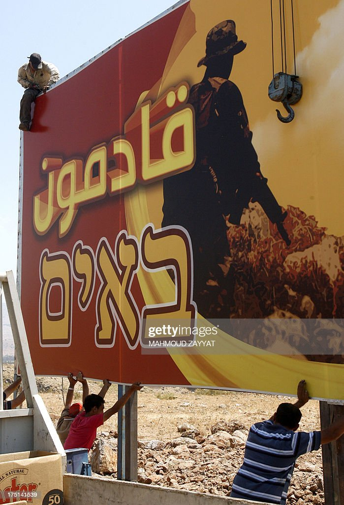 Lebanese men put up a large billboard sponsored by Hezbollah reading in Arabic (top) and Hebrew (bottom), 'we are coming' as they prepare for al-Quds day celebrations on August 1, 2013 in the village of Wazzani on the border between Lebanon and Israel. Al-Quds day is an annual event on the last Friday of the Muslim month of Ramadan where believers fast during daylight hours, expressing solidarity with the Palestinian people and opposing Zionism as well as Israel's control of Jerusalem.