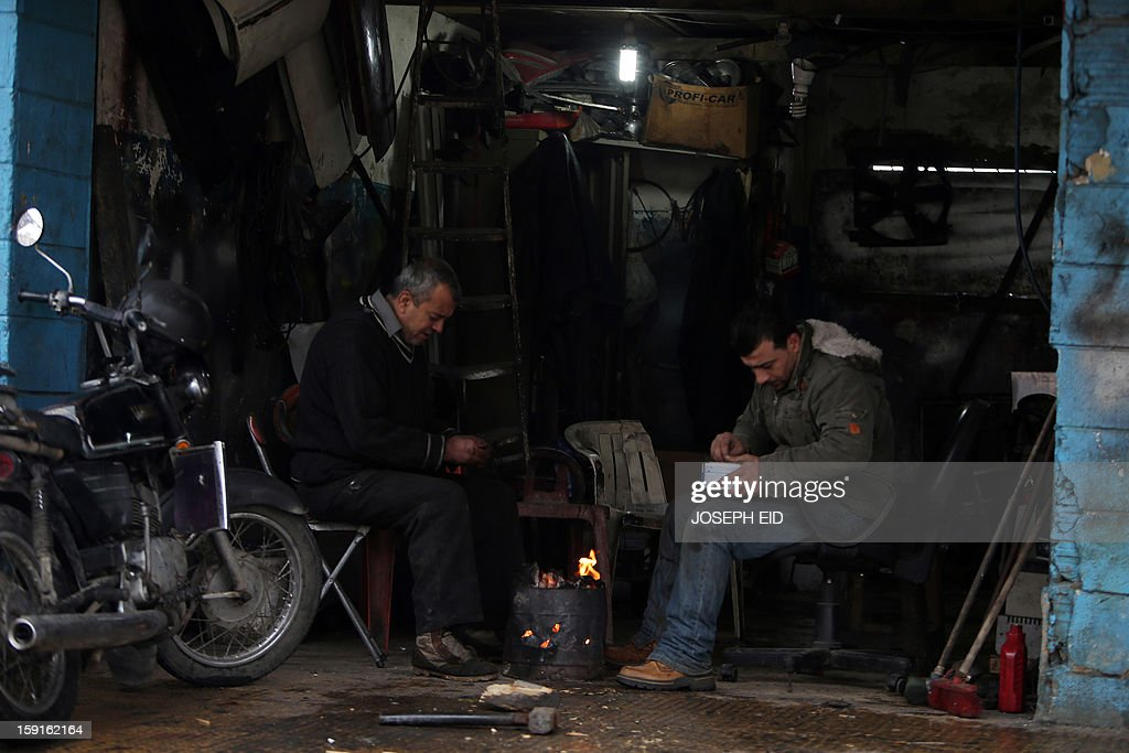 Lebanese men sit by a fire at their workshop in a southern suburb of Beirut on January 9, 2013, as heavy rains and high speed winds hit the country. A met office official at Beirut airport said the storm would continue and that lower temperatures would result in snowfall in the mountains as low as 300 metres.