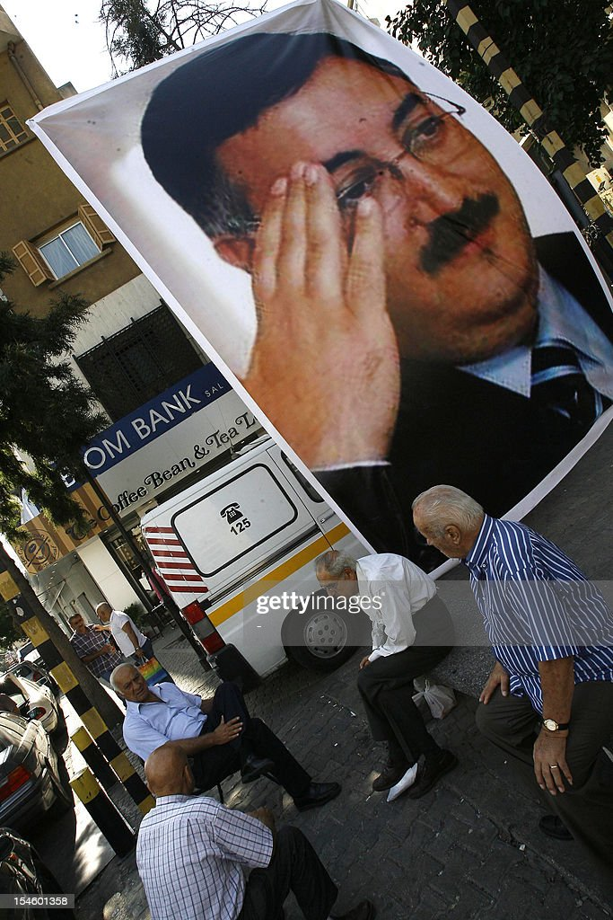 Lebanese men sit next to a poster of slain police intelligence chief General Wissam al-Hassan on October 23, 2012 near the site of a car bomb blast that killed him in Beirut's Christian neighbourhood of Ashrafieh. The United States will send a Federal Bureau of Investigation team to help Lebanon probe the Beirut car bombing that killed Hassan, officials said. AFP PHOTO/STR
