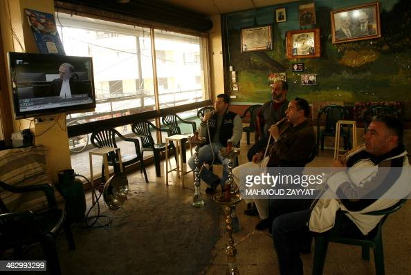 Lebanese men smoke waterpipes as they watch the opening of the trial in absentia of four members of the Hezbollah Shiite movement accused of...