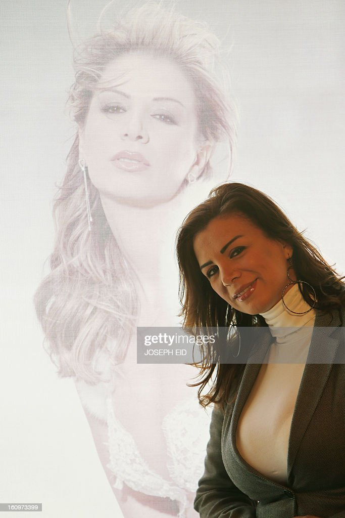 Lebanese model and modeling agency owner Nathaly Fadlallah poses by a curtain picturing her portrait at her office in Beirut on January 29, 2013. Fadlallah is one of two fashion models who have have stirred controversy and set a precedent by announcing that they will run in the upcoming parliamentary elections in spring.