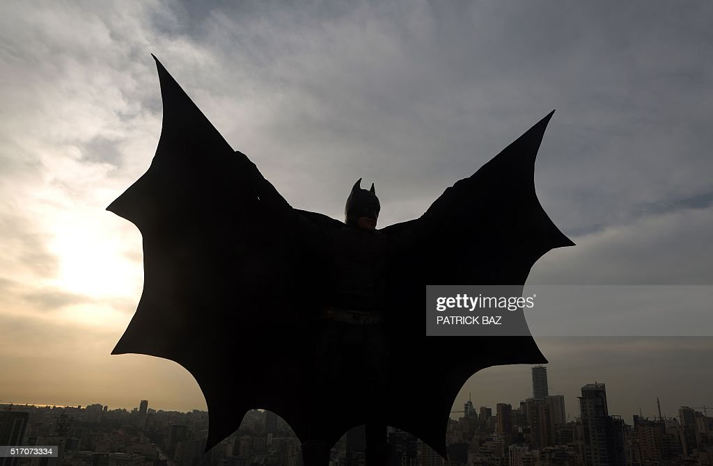 Lebanese model dressed as Batman plays on the rooftop of a building during a photoshoot in the capital Beirut on March 23 2016 / AFP / PATRICK BAZ