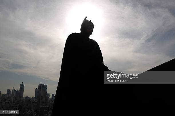 A Lebanese model dressed as Batman plays on the rooftop of a building during a photoshoot in the capital Beirut on March 23 2016 / AFP / PATRICK BAZ